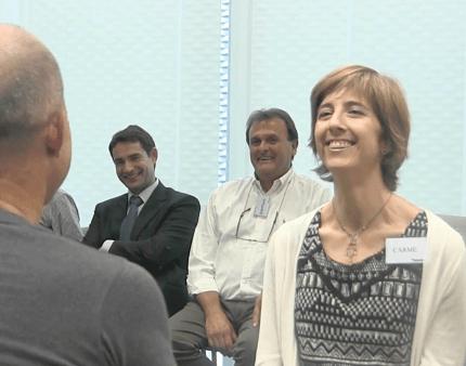 Coach riendo en una sesión de coaching empresarial.